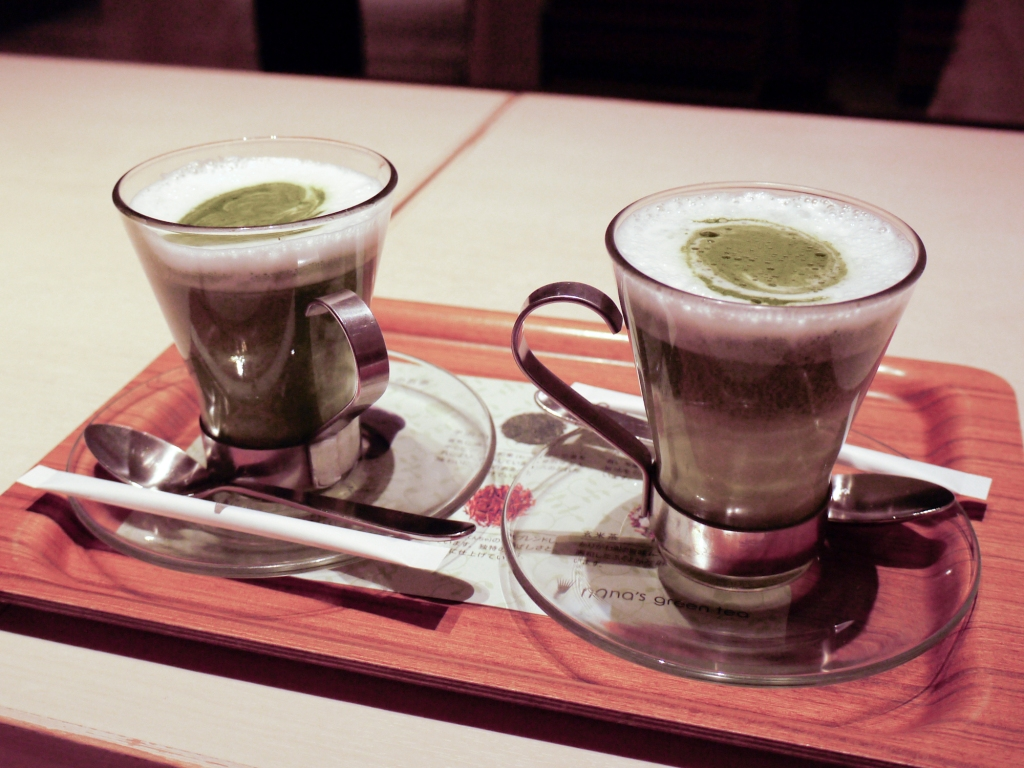 Two green tea lattes on a tray